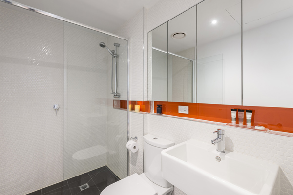 clean en suite bathroom with large disabled access shower, toilet and large mirror in 1 bedroom apartment with Wi-Fi at Oaks South Yarra hotel, Melbourne city, Victoria, Australia