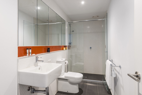 clean en suite bathroom with spacious disabled access shower, toilet, large mirror and fresh towels in Studio Apartment at Oaks South Yarra hotel, Melbourne city, Victoria, Australia