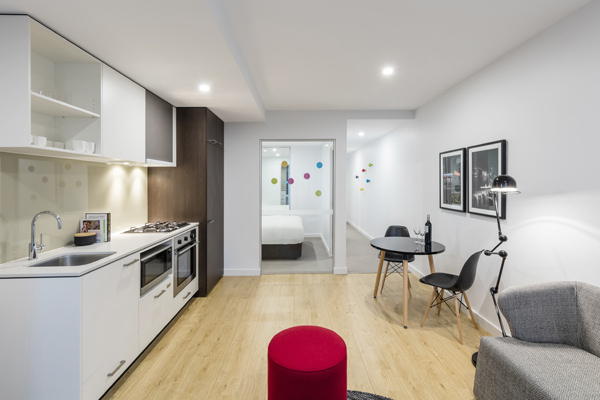 big living room in 1 bedroom hotel apartment with desk and office chair for corporate travellers to do work on while visiting Melbourne city on a business trip
