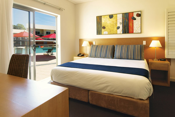 comfortable double bed in air conditioned 2 bedroom poolside apartment at Oaks Broome hotel, Western Australia