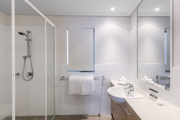 shower in clean en suite bathroom of popular hotel room in Broome, WA with toilet, fresh towels and large mirror