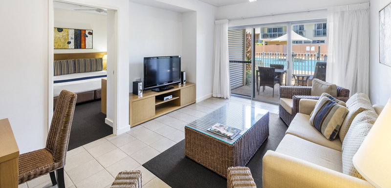 plasma TV with Foxtel in front of comfortable couch in air conditioned living room of 1 bedroom apartment with private balcony at Oaks Broome hotel in Western Australia