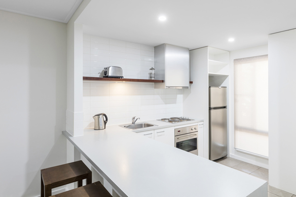 kitchen with big fridge, freezer, microwave, kettle and toaster for hotel guests staying in a 2 Bedroom Apartment at Oaks Cable Beach Sanctuary in Broome, Western Australia