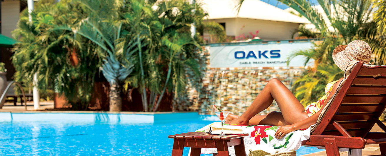 Oaks hotels air NZ Airpoints promotion banner image with woman by swimming pool at hotel on holiday in sunshine