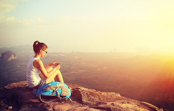 Young woman sitting on Wolfgang Peak hike view mountain near Moranbah hotels at sunset during vacation to Queensland, Australia