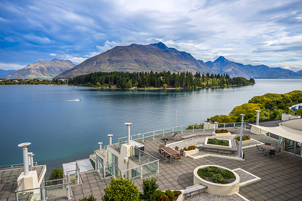 hotel guests in large courtyard of Oaks Club Resort next to Lake Wakatipu in Queenstown with The Remarkables mountain range in background during midday