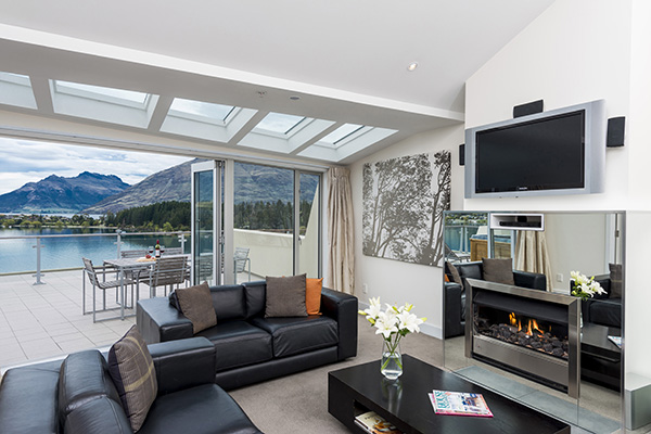 beautiful living room with Wi-Fi, Sky TV, fireplace and spacious outdoor balcony with views of Queenstown mountains in 2 Bedroom Lake View Apartment at Oaks Club Resort hotel in Queenstown, New Zealand