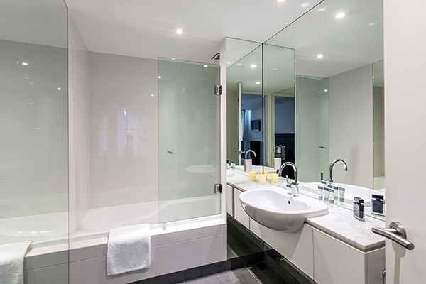 large shower, bathtub, toilet, basin, frsh towels and mirror in clean en suite bathroom of 2 Bedroom Apartment at Oaks Club Resort hotel in Queenstown, New Zealand