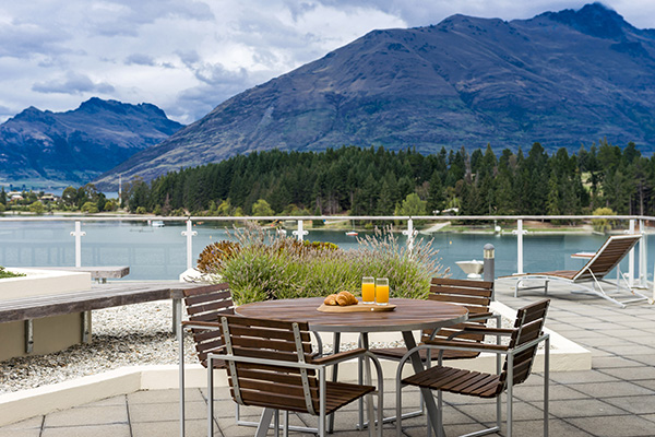 spacious private hotel balcony with vegetarian menu options on table and views of Lake Wakatipu at Oaks Club Resort in Queenstown, New Zealand