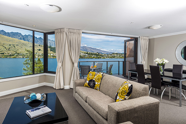2 Bedroom Holiday Apartment in Queenstown resort in living room with heating, comfortable couches, Sky TV and private balcony outside with table, chairs and views of Lake Wakatipu