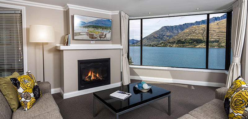 large fireplace in living room with Sky TV and Wi-Fi access in 4 bedroom penthouse apartment at Oaks Shores hotel with views of Lake Wakatipu in Queenstown, New Zealand