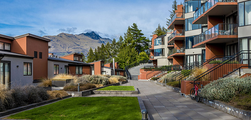 pathway outside Oaks Shores hotel apartments in Queenstown, New Zealand with views of The Remarkables mountain range and blue skies in the distance