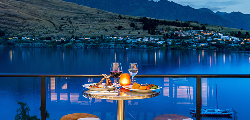 couple eating steak and chips on table on balcony outside Shores Restaurant during romantic holiday to Queenstown, New Zealand