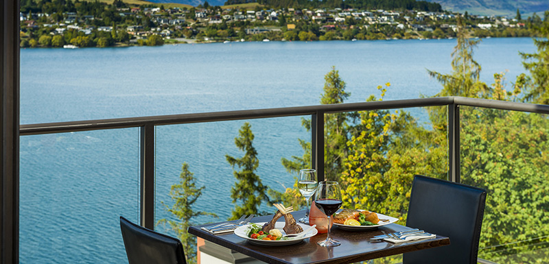 vegan menu options from Shores Restaurant and a bottle of wine on table on balcony with views of The Remarkables mountains in Queenstown, New Zealand during lunch time