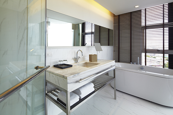 large en suite bathroom with clean towels, disabled access shower, toilet and bath tub in 2 Bedroom Apartment suite at Oaks Bangkok Sathorn hotel in Thailand