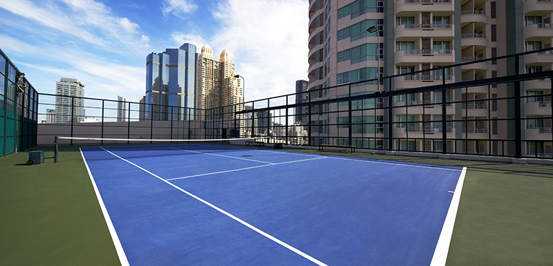 tennis court at Oaks Bangkok Sathorn hotel in Thailand during summer with blue skies in background close to the city CBD