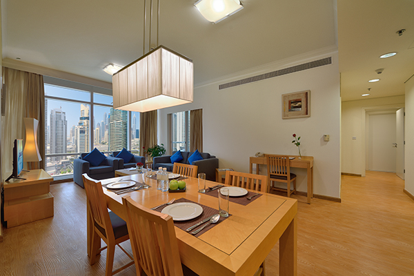 dining table with cutlery on it in spacious air conditioned living room of Deluxe 1 Bedroom holiday apartment with private balcony at Oaks Liwa Heights hotel in Dubai, United Arab Emirates
