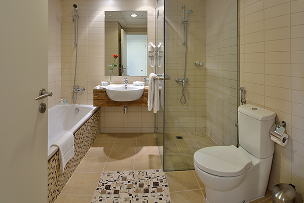 clean en suite bathroom with toilet, shower, bath tub, sink and big mirror in Premier 1 Bedroom holiday apartment at Oaks Liwa Heights hotel in Dubai, United Arab Emirates
