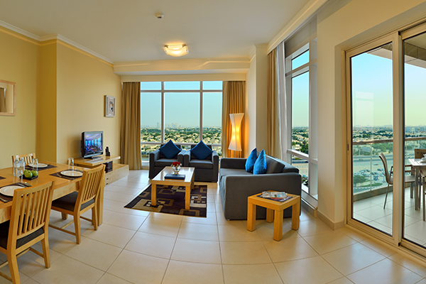 air conditioned living room with WiFi access, satellite TV and glass sliding doors leading to private balcony with furniture outside Premier 1 Bedroom holiday apartment at Oaks Liwa Heights hotel in Dubai, United Arab Emirates
